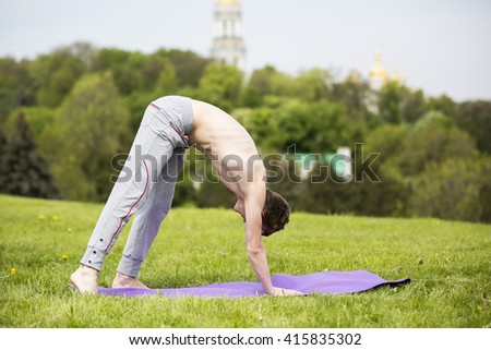 Man doing yoga in nature. Young man doing yoga fitness exercise outdoor in beautiful mountains landscape. Morning sunrise. Meditation and Relax - stock photo