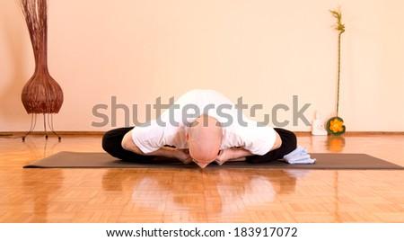 Man doing yoga indoors, - stock photo