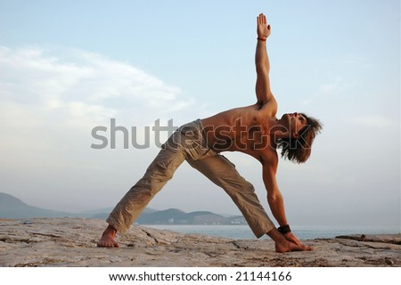 Man doing yoga outdoors. Trikonasana. Side view. - stock photo