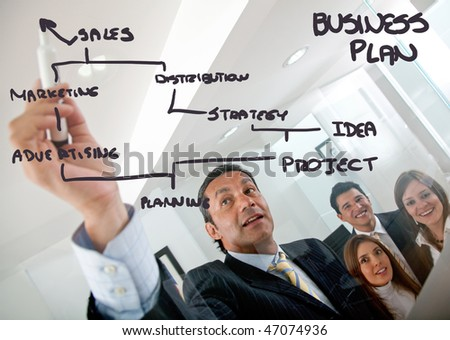 man drawing a business plan and showing it to a group