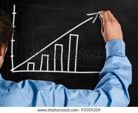 Man drawing a rising arrow on a blackboard