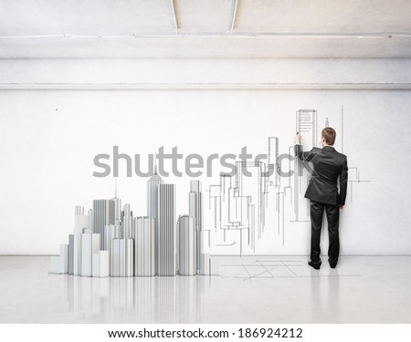 Man drawing city on a wall. Model of a city on a floor. - stock photo