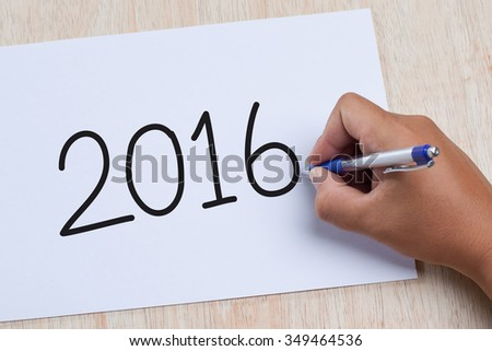 Man drawing 2016 concept on white paper. - stock photo