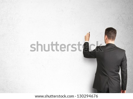 man drawing on concrete wall