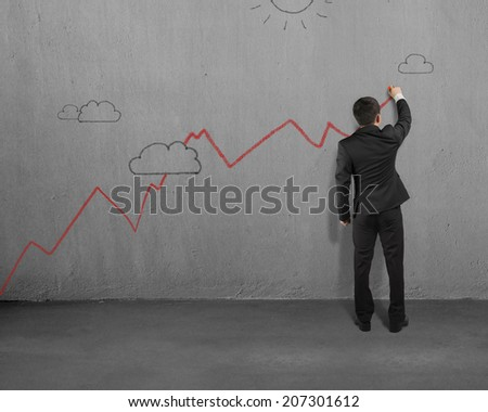 Man drawing red growing trend on concrete wall - stock photo