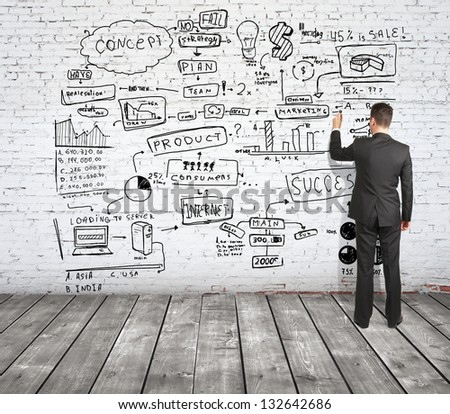 man drawing strategy on brick wall - stock photo