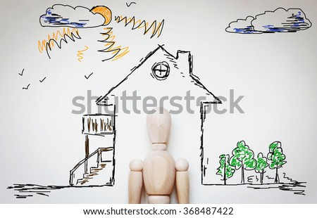 Man dreaming about cozy home. Abstract image with wooden puppet - stock photo