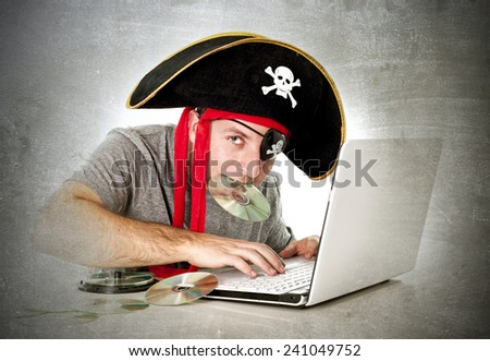 man dressed as pirate with CD in his mouth at computer laptop downloading music files and movies in copyright violation and illegal internet piracy concept - stock photo