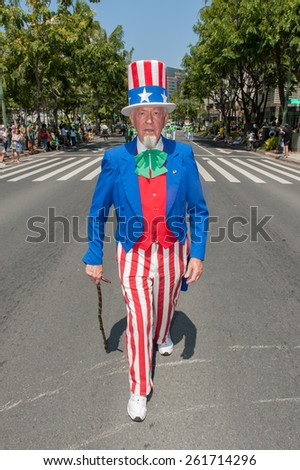 Man dressed as Uncle Sam with a green shamrock bow tie walks on Kalakaua Avenue in the  St. Patrick's Day Parade in Waikiki on March 17, 2015. - stock photo