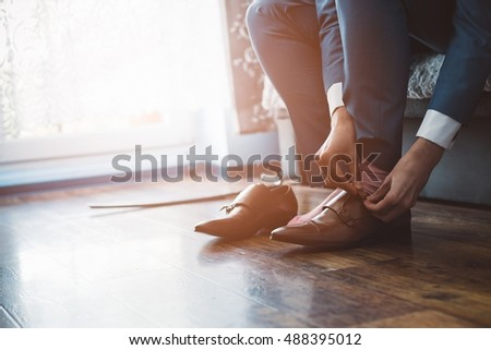 Man dressed in a suit fastens leather shoes. Wedding preparations