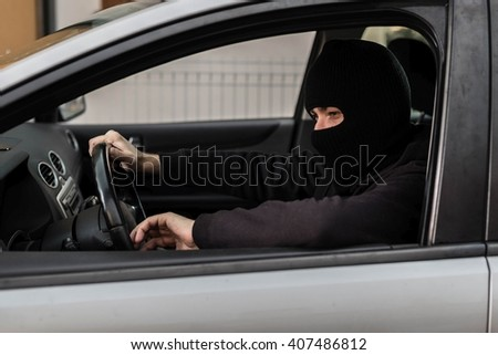 Man dressed in black with a balaclava on his head driving a stolen car. Car thief, car theft concept - stock photo