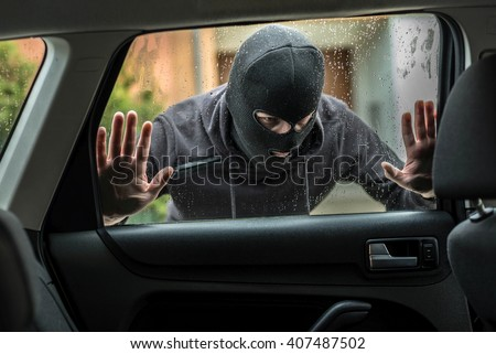 Man dressed in black with a balaclava on his head looking through car window and wondering how to break into this car. Car thief, car theft concept - stock photo