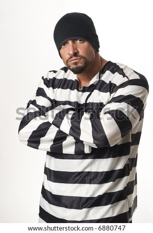 Man dressed in convict costume with rings and beanie - stock photo