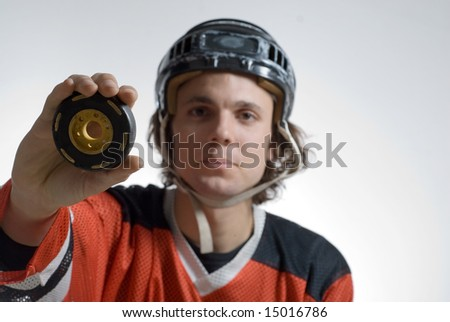 Man dressed in hockey gear holding a hockey puck with a funny expression on his face. Horizontally framed photograph. - stock photo