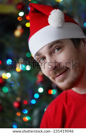 man dressed in red shirt and christmas cap - stock photo