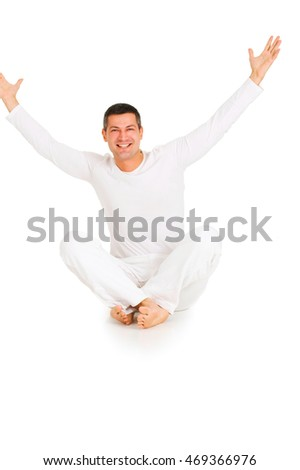 man dressed in white sitting on the floor with arms up