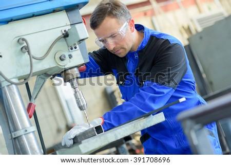 Man drilling through metal - stock photo