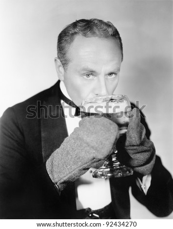 Man drinking a big glass of cold beer with mittens - stock photo