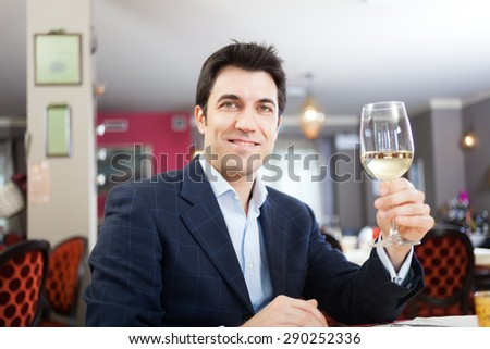 Man drinking a glass of white wine in a restaurant - stock photo