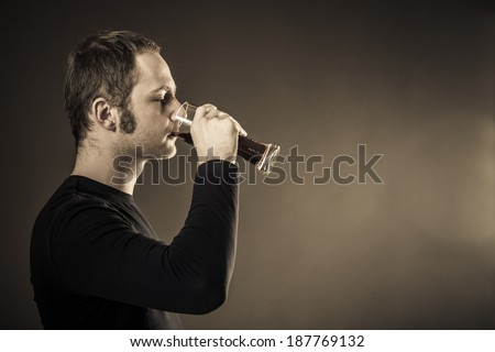 Man drinking beer on dark background. Closeup - stock photo
