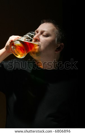 Man drinking beer over black background with space for your own text below - stock photo