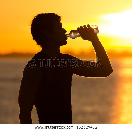Man drinking bottle of water on the beach at sunrise - stock photo