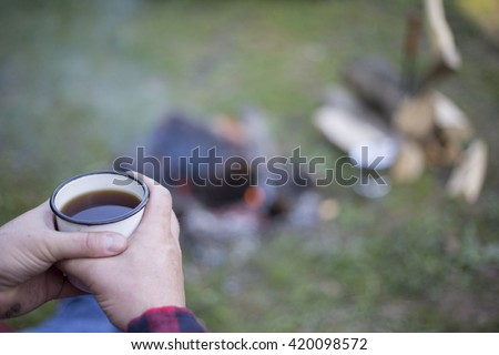 Man drinking coffee by the fire at a campsite on the river bank. - stock photo