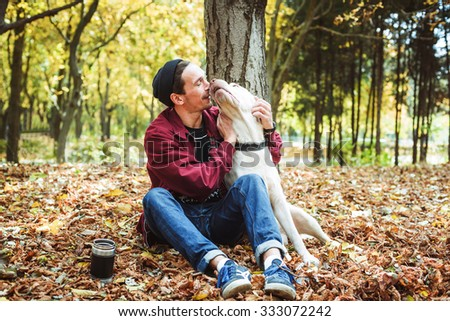 man drinking coffee in park and playing with labrador dog - stock photo