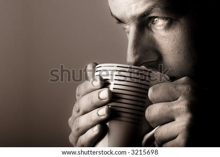 Man drinking warm beverage. Low key image. Sepia toned. - stock photo