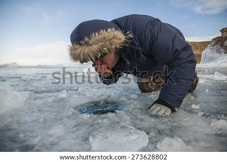 Man drinking water from a hand hole of Lake Baikal - stock photo