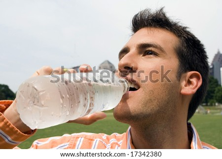 man drinking water in a city park