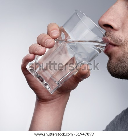 Man drinking water isolated in studio - stock photo