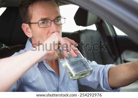 Man drinking wine while driving in his car - stock photo