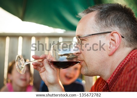 Man drinking wine with his family