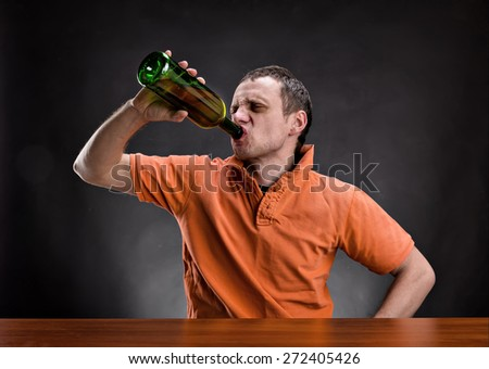 Man drinks alcohol over gray - stock photo