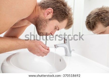 Man drinks tap water from the bathroom sink - stock photo