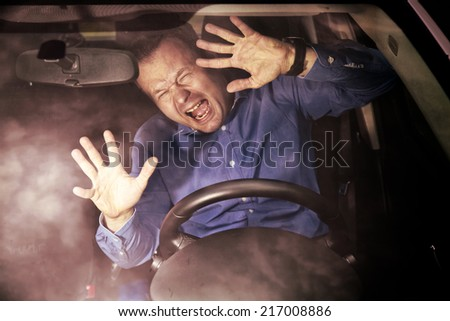 Man driver during moment of car accident inside of a car (hard grunge effect)
