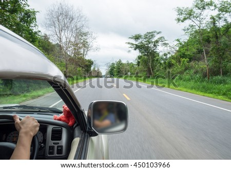 Man driver holding steering wheel right on rural road shady