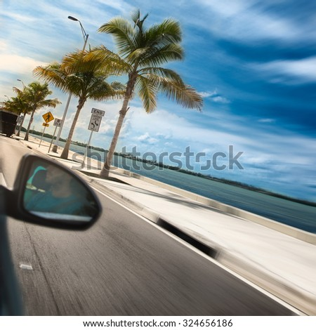 Man driving a car across paradise road with palms and ocean - stock photo