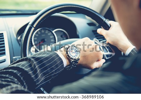 Man driving a car and looking at watch ,business concept ,vintage tone - stock photo