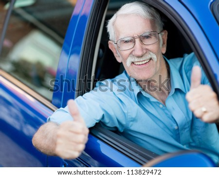 Man driving a car and showing thumbs up - stock photo