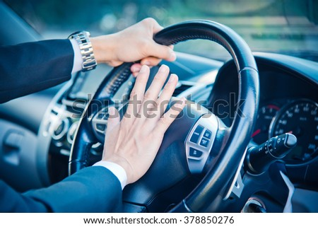 Man driving a car with hand on horn button, vintage color tone