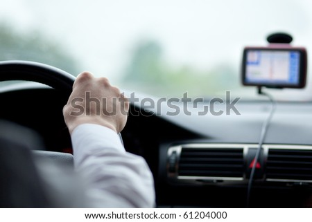 man driving a car with his hands on the steering wheel, using a satelite navigation/GPS