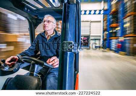 man driving a forklift through a warehouse in a factory - stock photo