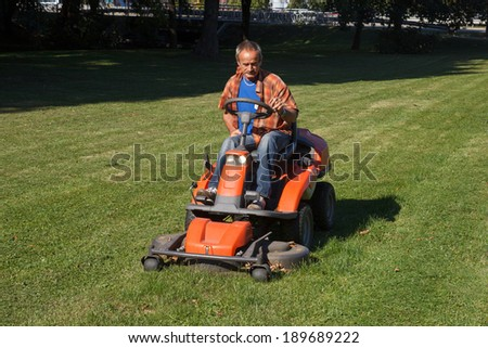 man driving a lawn mower in the city park - stock photo