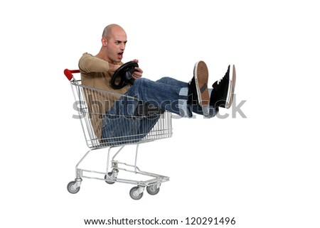 Man driving a shopping trolley - stock photo
