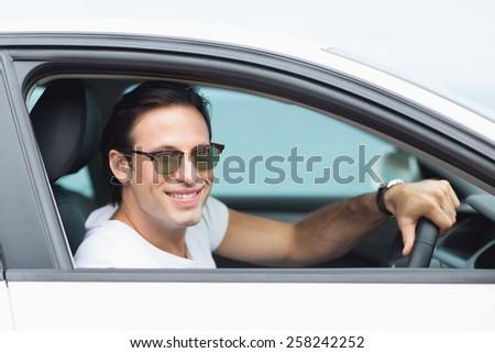 Man driving and smiling at camera in his car - stock photo