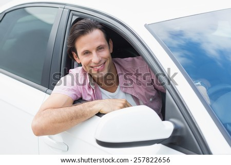Man driving and smiling in his car - stock photo