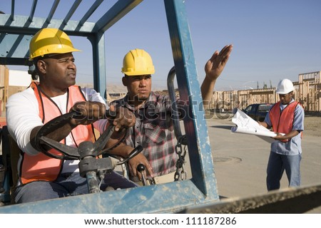 Man driving bulldozer at construction site among other workers - stock photo