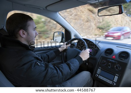 Man driving car in  mountain road. - stock photo